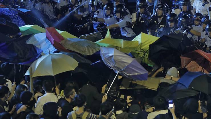 Die Demonstranten versuchen sich mit Regenschirmen gegen den Pfefferspray der Polizisten zu wehren.
