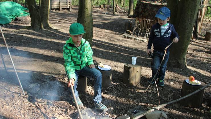 2 Jungs achten darauf das das Feuer nicht ausgeht.