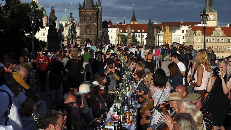 dpatopbilder - Anwohner sitzen zum Essen an einem 500 Meter langen Tisch auf der mittelalterlichen Karlsbrücke, nachdem die Einschränkungen während der Corona-Pandemie gelockert wurden. Foto: Petr David Josek/AP/dpa