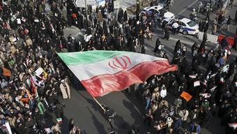 Pro-Regierungs-Demonstranten im nordostiranischen Maschhad schwenken die Nationalflagge.