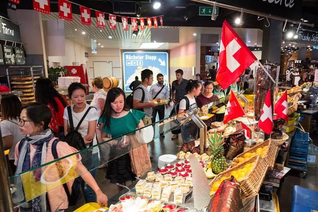 Eine Mitarbeiterin führt auf Wunsch chinesische Touristen durch die Läden.