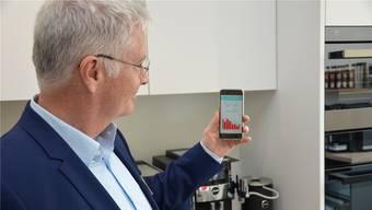 Peter Lehmann, Geschäftsleiter IBW, blickt auf sein Handy. Über eine App soll der Nutzer zukünftig jederzeit Informationen über den Stromverbrauch abrufen können. Zum Beispiel, ob die Herdplatte ausgeschaltet ist.