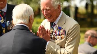 Prinz Charles (r), Prinz von Wales, begrüßt anlässlich des Tages der Kapitulation Japans im Zweiten Weltkrieg am National Memorial Arboretum einen Veteranen. Foto: Oli Scarff/PA Wire/dpa