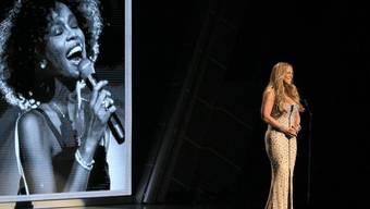 Mariah Carey auf der Bühne der BET Awards, im Hintergrund eine Aufnahme Whitney Houstons