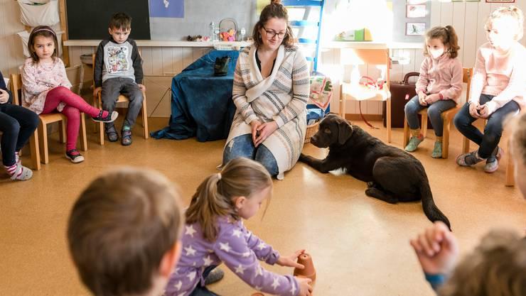 Ein Kindergartenkind darf ein Leckerli unter einem Tontopf verstecken.