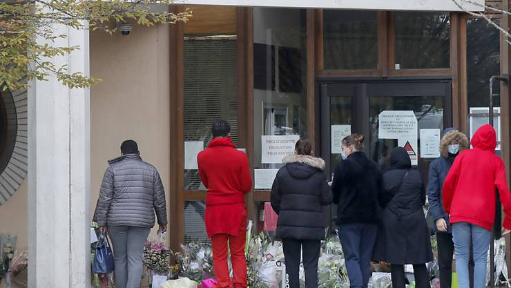 Schüler gedenken vor einer Schule, auf der der Schriftzug «Liberté - Egalité - Fraternité» (Freiheit - Gleichheit - Brüderlichkeit) zu lesen ist, einem Lehrer, der bei einer mutmaßlich terroristisch motivierten Tat ermordet wurde. Foto: Michel Euler/AP/dpa