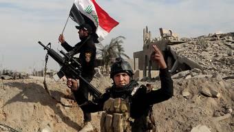 Irakische Soldaten pflanzen ihre Flagge auf ein Gebäude in der vom IS zurückeroberten Stadt Ramadi. (Archivbild)