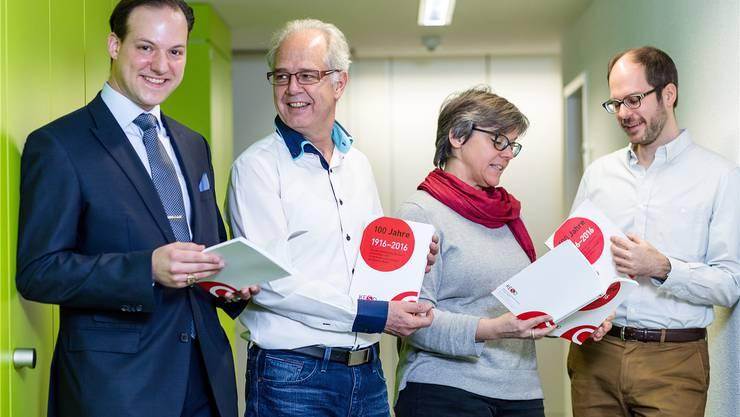 Norbert Stichert (KESD-Präsident), Reto Bertschi (Berufsbeistand und Co-Stellenleiter), Regula Dell'Anno (Vorstandsmitglied) und Historiker Ernst Guggisberg blättern die Jubiläumsschrift durch.