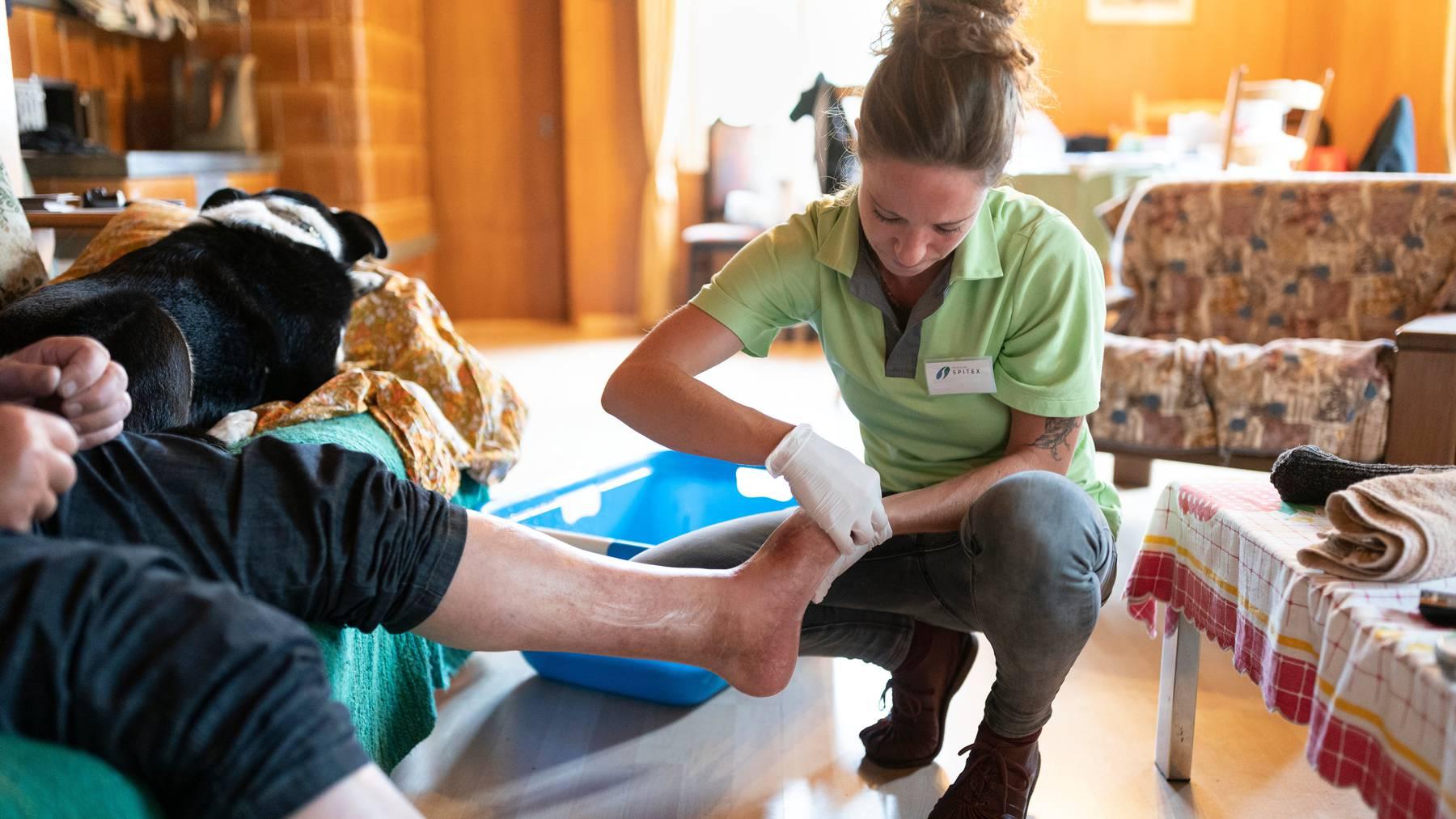 Eine Spitex-Mitarbeiterin reinigt und kontrolliert die Füsse eines Seniors. (Symbolbild)