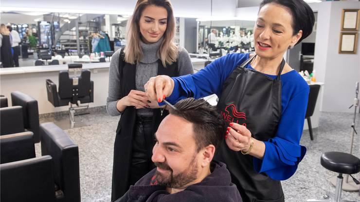 Marianne Binder hilft zu Wahlkampf-Zwecken bei Coiffeur Ramon Grimm (auf dem Bild als Testkunde) unter Anleitung von Samire Korqa in Baden aus.