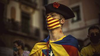 Ein Mann trägt eine Maske mit den Farben der katalanischen Unabhängigkeitsflagge in Barcelona. Seit 1714 begehen die Katalanen jedes Jahr am 11.09. ihren Nationalfeiertag - die «Diada». Foto: Matthias Oesterle/ZUMA Wire/dpa