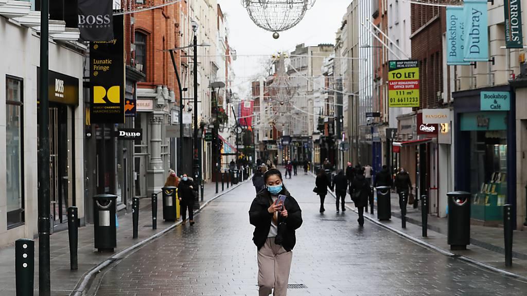 Passanten mit Mund-Nasen-Bedeckungen gehen über die Grafton Street in Dublin. Foto: Brian Lawless/PA Wire/dpa