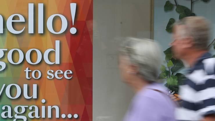 ARCHIV - Ein Mann und eine Frau passieren ein Schaufenster, in dem ein Plakat mit der Aufschrift «hello! good to see you again...» («Hallo! Gut, sie wieder zu sehen...») hängt. Foto: Andrew Matthews/PA Wire/dpa