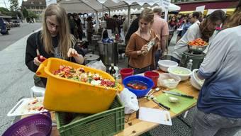 Personen ruesten Gemuese, am Anlass Bern tischt auf - ein Fest aus ueberschuessigen Lebensmitteln.JPG