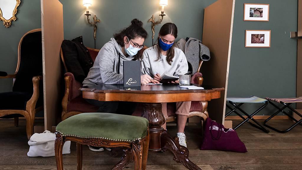 Zwei Frauen füllen die Informationen für das Contact Tracing in einem Restaurant noch schriftlich aus. SocialPass bietet dafür die digitale Lösung. Doch damit erhalten die Gesundheitsbehörden fast beliebigen Zugang zu den Daten, kritisiert der Datenschutzbeauftragte.