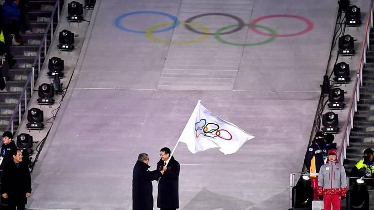 IOC-Präsident Thomas Bach überreicht die olympische Flagge an den Bürgermeister von Peking, Ausrichter der nächsten Winterspiele in vier Jahren