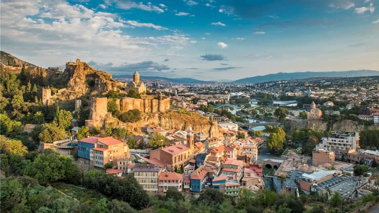 Aus der Ferne betrachtet wirkt Tiflis wie aus dem Bilderbuch, doch aus der Nähe zeigt sich auch Zerfall. Getty Images