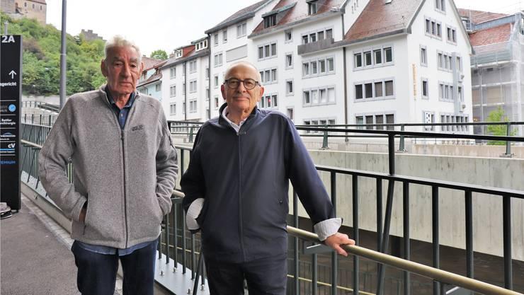 Heinz Müller (l.) und Walter Obrist fordern, dass die Kosten für die Schäden an ihren Häusern (Hintergrund) übernommen werden.