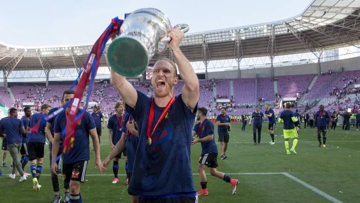 Michael Lang feiert mit dem Cuppokal in Genf. Der Verteidiger spielte eine spitzen Saison.