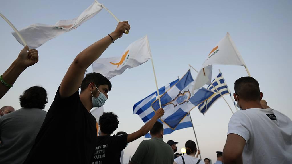 Bewohner der verlassenen Stadt Varosha oder Famagusta halten zypriotische und griechische Fahnen während eines Protestes gegen die türkische Regierung. Die Europäische Union droht der Türkei wegen der jüngsten Eskalation des Zypernkonflikts mit Sanktionen. Foto: Petros Karadjias/AP/dpa