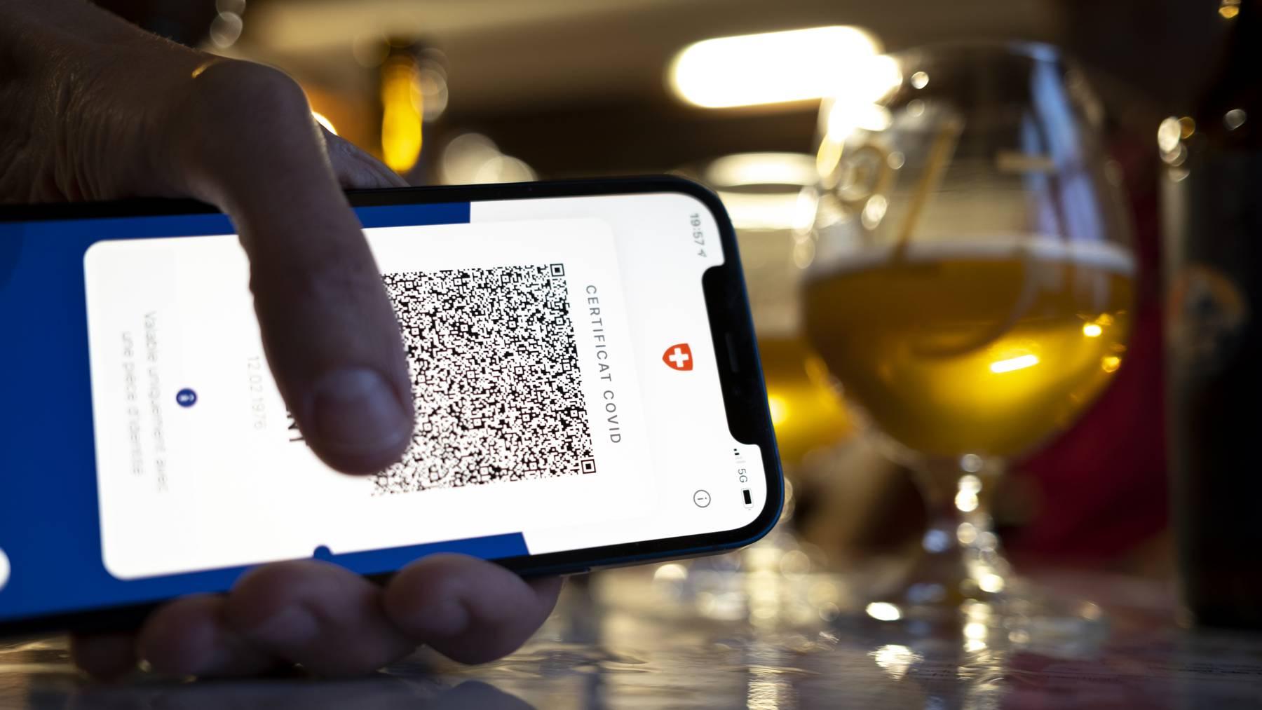 Une personne tient dans sa main un smartphone avec l'application Certifact Covid suisse dans un restaurant ce vendredi 10 septembre 2021 a Rances dans le canton de Vaud. Des ce lundi 13 septembre, il faudra montrer le code QR sur l'app ou sur papier du certificat Covid pour se rendre dans un restaurant, au cinema ou encore dans un fitness. // Covid-Zertifikat