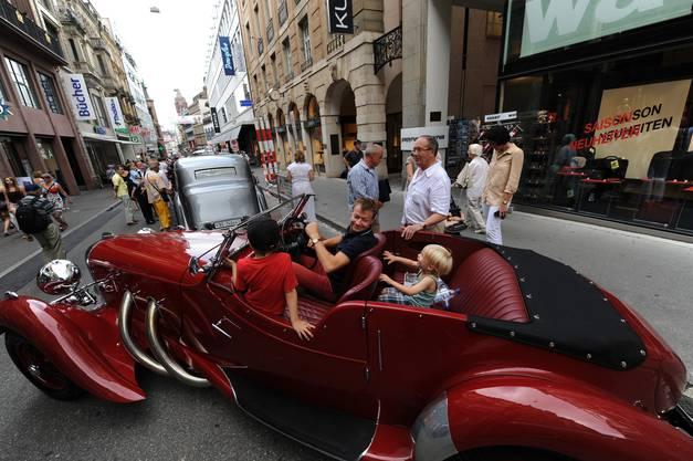 Diese Kinder geniessen die Fahrt im antiken Auto
