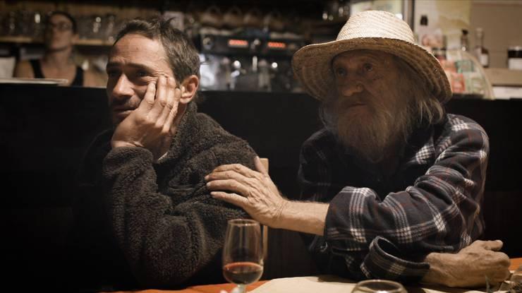 Fabiano und sein Vater Philippe, der in den 1970er-Jahren auf der Suche nach alternativen Lebensformen ins Onsernonetal kam. Sie schauen sich in Locarno eine Fernsehreportage zum Kriminalfall an.