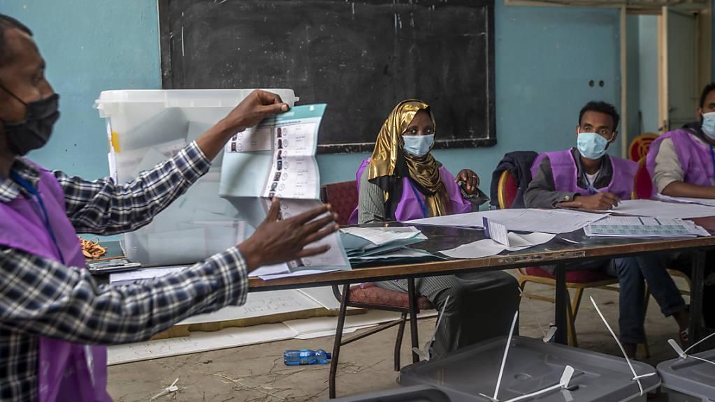 Wahlhelfer zählen Stimmen in einem Wahllokal. Die Parlamentswahl in Äthiopien wird in der Region Sidama um einen zweiten Tag verlängert. Am Wahltag habe es an Stimmzetteln gefehlt, sagte die Wahlkommission am späten Montagabend.