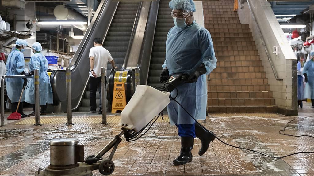 Mitarbeiter in Schutzkleidung desinfizieren einen sogenannten Nassmarkt in Hongkong. Foto: May James/ZUMA Wire/dpa