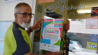 Vigi Dörig, OK-Präsident der Siga 19, hängt selbst die Plakate auf.