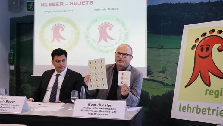 Wirtschaftskammer-Direktor Christoph Buser und Beat Huesler Präsident der Konferenz der Gewerbe- und Industrievereine (KGIV) präsentieren die Etiketten und Aufkleber.