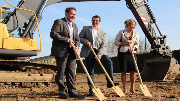 Hier entsteht in acht Monaten ein Minergie-Neubau aus Holz. Die Geschäftsführer der Profi Office GmbH, Samuel und Cornelia Vonlanthen, und Gemeinderat Matthias Jauslin setzen zum Spatenstich an.ROB