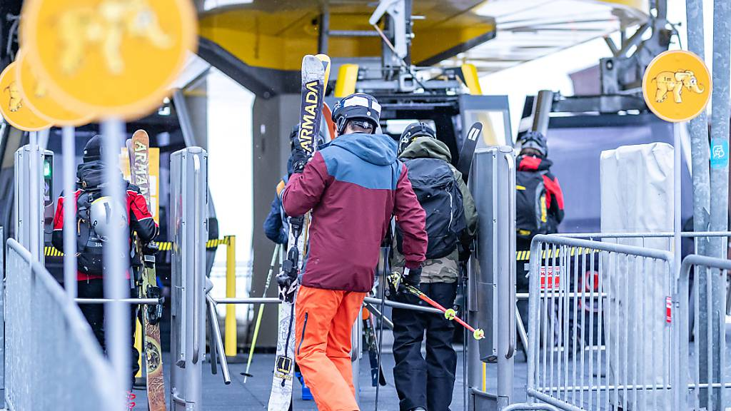 Menschen gehen mit ihren Skiern zu einer Gondel in der Talstation des Skigebiets Zillertal Arena. Foto: Expa/Johann Groder/APA/dpa
