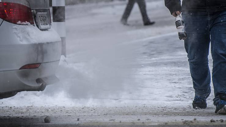Ein Auto stösst Abgase neben einem Fussgänger aus (Archivbild)
