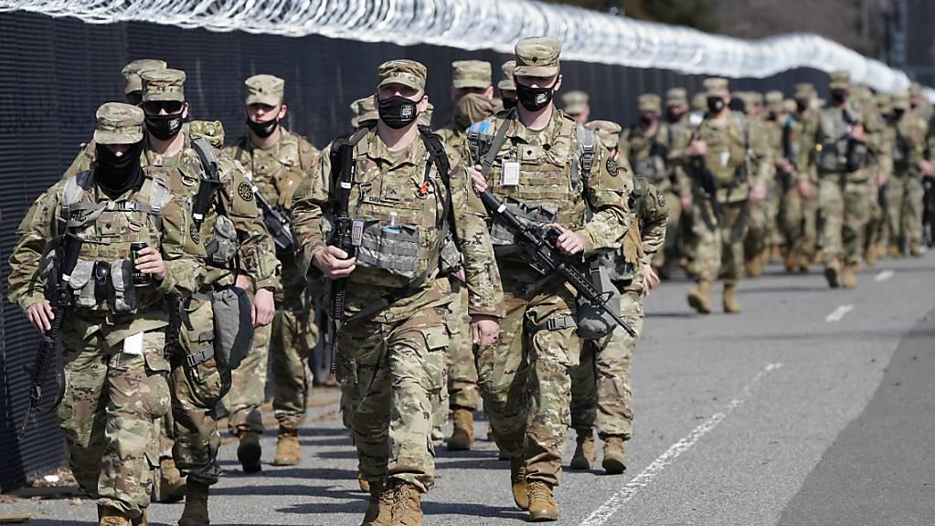 Soldaten der Nationalgarde gehen entlang eines Sicherheitszauns vor dem Kapitol. US-Sicherheitskräfte haben nach Hinweisen auf einen möglichen erneuten Angriff auf das US-Kapitol die Sicherheitsvorkehrungen am Sitz des Kongresses verschärft. Foto: Jacquelyn Martin/AP/dpa