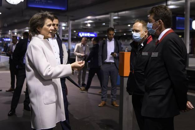 Bundespräsidentin Simonetta Sommaruga spricht mit zwei Mitarbeitern bei einem Besuch des Bahnhofs Bern.