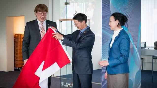 Reinhold Lückhardt übergibt Altankhuyag Otgonbaatar eine Schweizer Flagge, rechts die Büroleiterin Khashba Tsevegmid, die Übersetzerin.