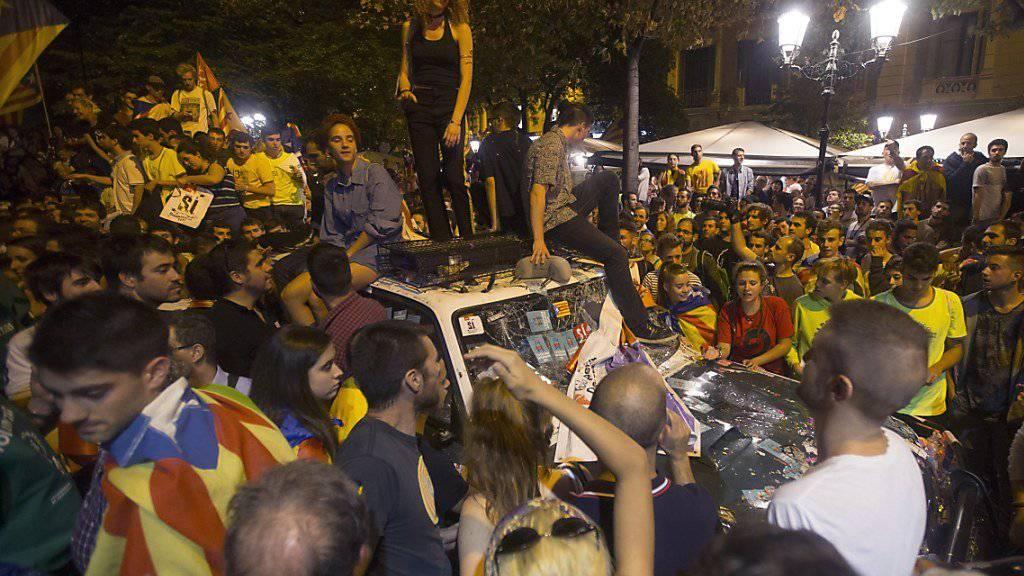 Demonstranten in Barcelona belagern ein Auto der spanischen Bundespolizei.