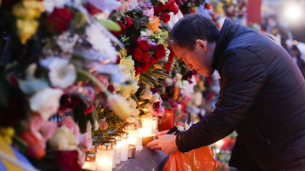 Ein Mann zündet in der Nähe des Tatorts in der Stockholmer Innenstadt in Gedenken an die Opfer des Anschlags eine Kerze an.