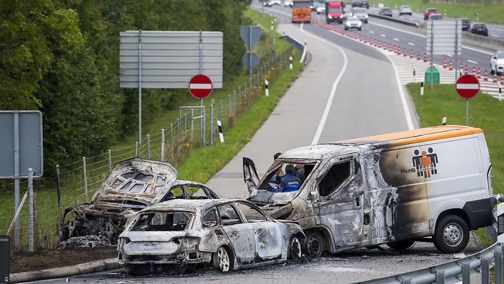 Drei Fahrzeuge brannten nach dem Überfall auf einen Geldtransporter auf der Ausfahrt der Autobahn A1 bei La Sarraz aus.