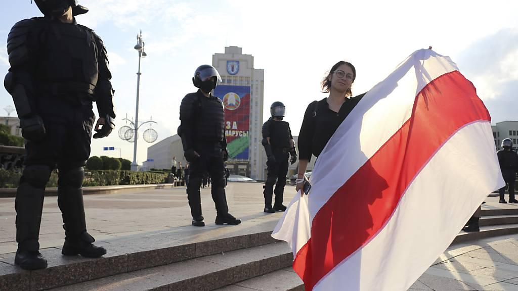 Eine Demonstrantin und Bereitschaftspolizisten stehen auf dem Unabhängigkeitsplatz in Minsk. Foto: -/AP/dpa
