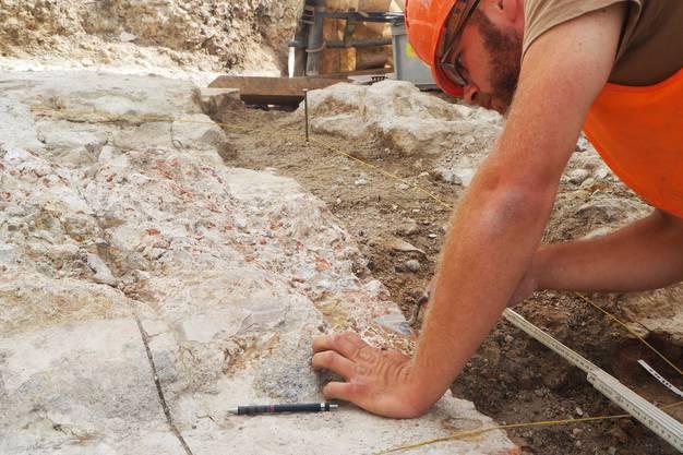 Mitarbeiter Erik Martin untersucht die Überreste des römischen Beckens.