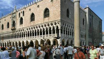 Touristen besuchen in Venedig den Markusplatz mit dem Dogenpalast. (Archivbild)