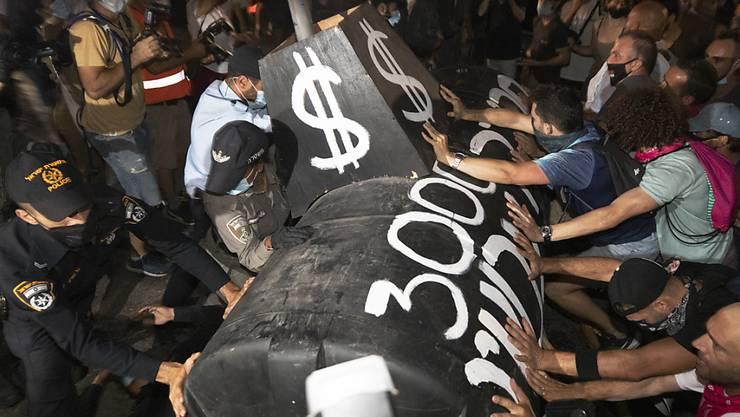 Demonstranten stoßen während eines Protests gegen den israelischen Ministerpräsidenten Netanjahu mit der Polizei zusammen. In der Küstenmetropole Tel Aviv trafen sich am Samstagabend Demonstranten unter anderem am zentralen Habima-Platz. Foto: Sebastian Scheiner/AP/dpa