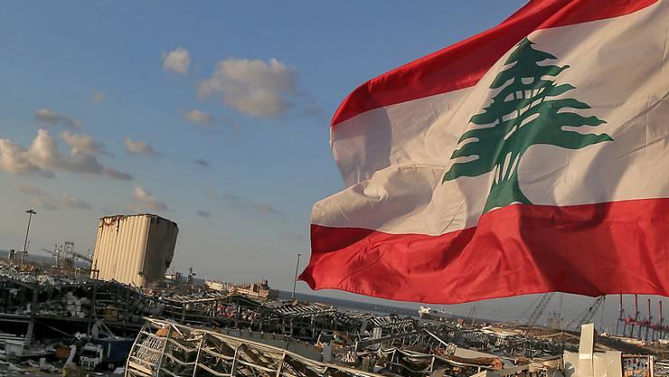 Eine libanesische Flagge weht in der Nähe der Stelle, an der eine Explosion am 4. August 2020 den Hafen von Beirut in die Luft sprengte. Foto: Marwan Naamani/dpa