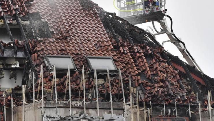 Feuerwehrmänner kämpfen gegen letzte Glutnester im Dachstock des Spitals in Bochum.