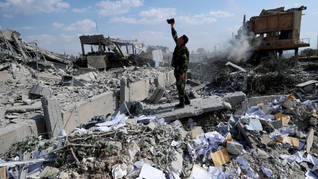 Verwüstung ohne Ende: Ein Mann filmt in der Nähe von Damaskus die Ruinen eines Forschungszentrums, das zuvor durch ausländische Streitkräfte zerbombt wurde. (Archiv)