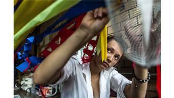 Eine Schülerin der Oberstufe befestigt Streifen aus Krepppapier an einen Ventilator — und macht damit Luft sichtbar.