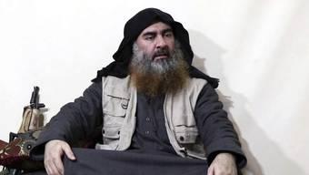 """In dem Video sitzt al-Bagdadi mit gekreuzten Beinen auf einem Kissen vor einer Waffe und spricht zu mehreren Anhängern der Terrormiliz. Darin erklärt er unter anderem, der Kampf gegen die """"Kreuzfahrer"""" werde lange dauern."""