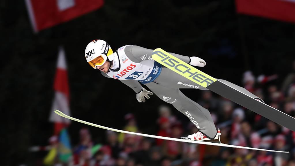Killian Peier fliegt an der Schweizer Fahne und den polnischen Zuschauern vorbei.